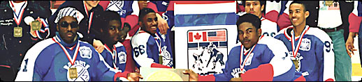 Photo of the Detroit Rockies celebrating their victory in Lake Placid, NY at the Can/AM Challenge Cup tournament.  The Rockies were the first, all-black (African American) hockey team to compete and win at the Midget AA level.